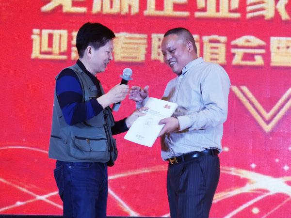 邓尚喜主席向芜湖企业家摄影协会会长朱政明赠送骑士奖获奖作品集